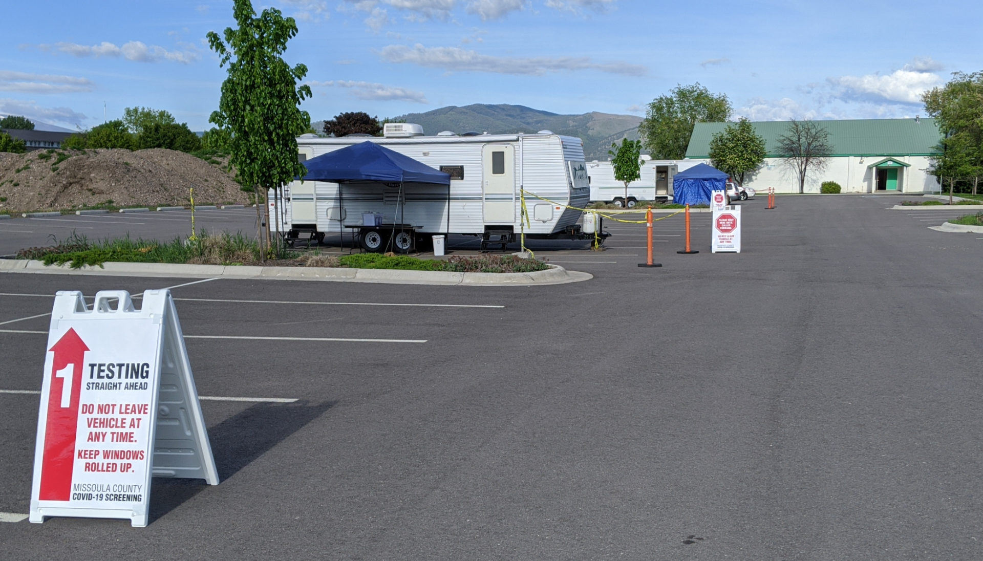 Photo of the COVID-19 Testing Site.  Two stations consisting of a camper trailer and a popup canopy where cars drive up to get tested.
