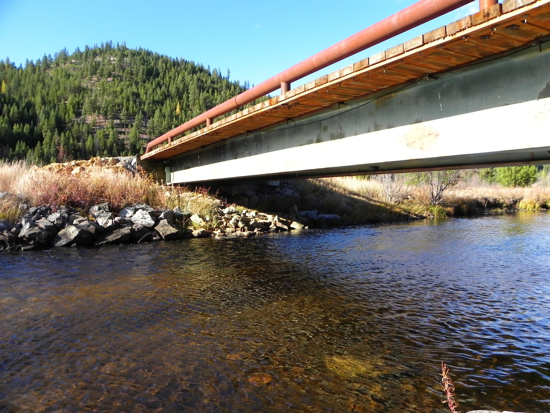 Missoula County creek and bridge with mountain.