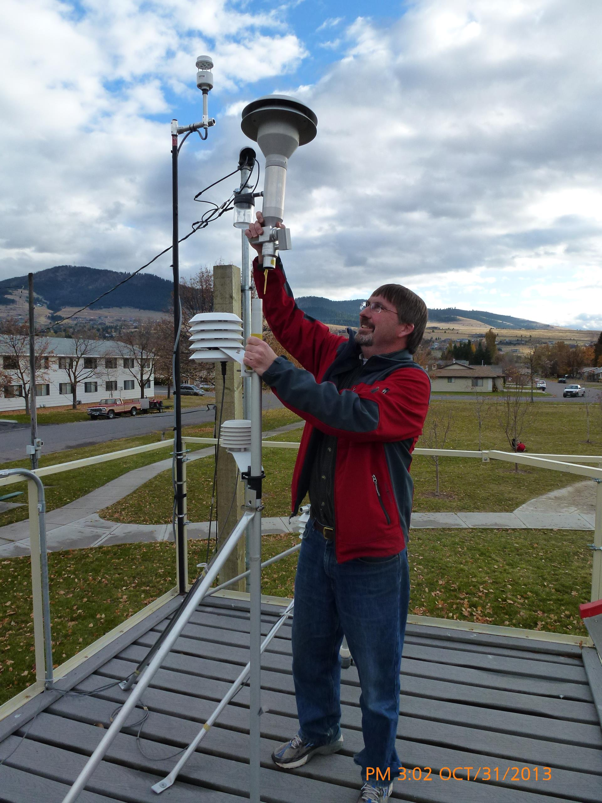 Air Quality Specialist Ben Schmidt conducts a flow check at an air quality monitor in Missoula